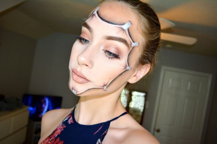 Chica creando maquillaje de fantasía en donde aparentemente se estira la cara