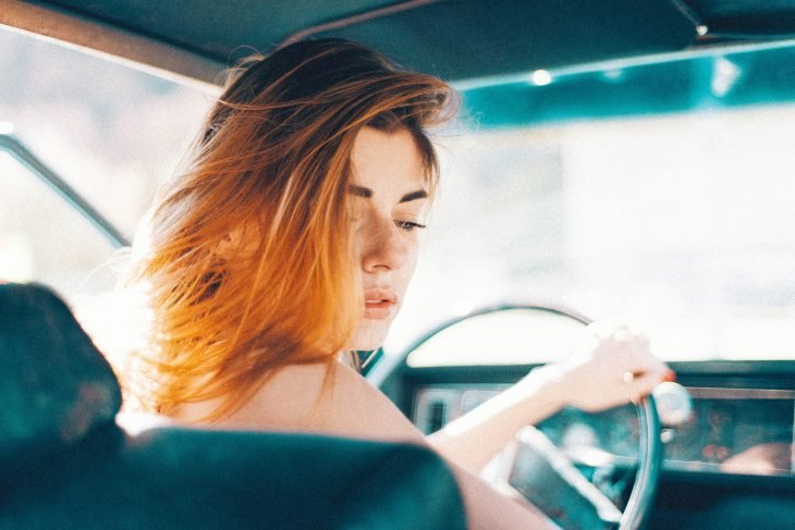 Chica peliroja manejando un auto