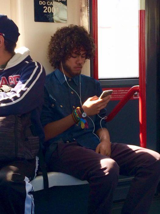 Chico en el metro viendo su celular
