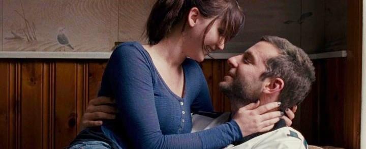 chica de blusa azul en brazos de hombre sonriendo