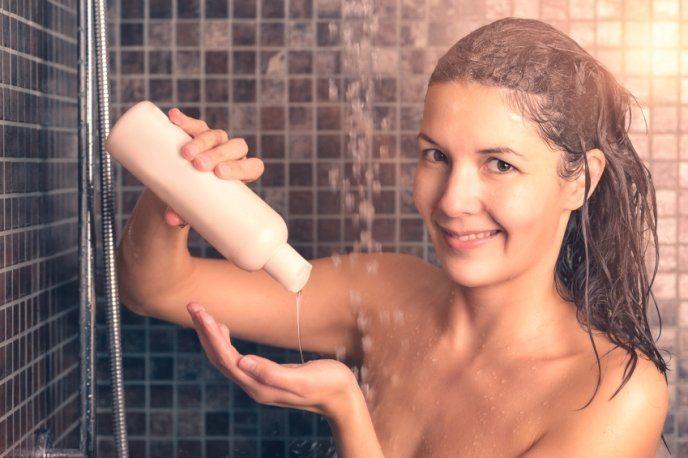 Chica en la ducha aplicando champú