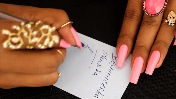 Chica con uñas largas tratando de escribir