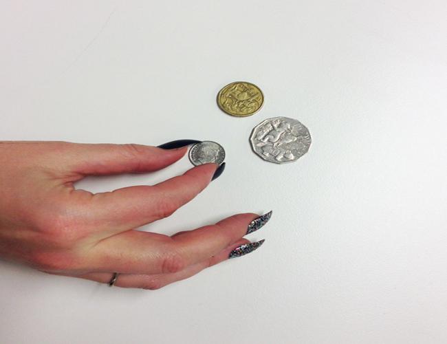 Chica intentando levantar las monedas de una superficie plana