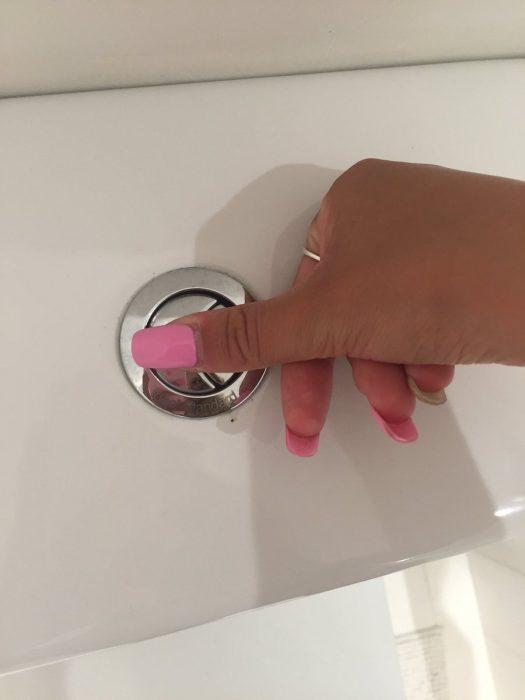 Chica tratando de oprimir un botón de inodoro con las uñas largas