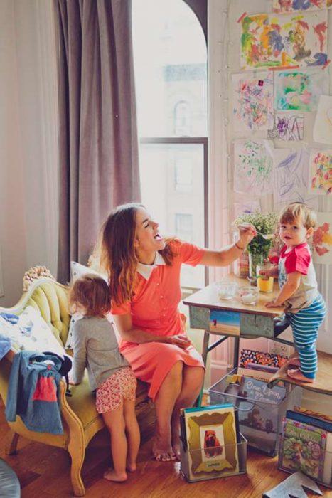 Chica jugando con sus hijos en un cuarto de juegos