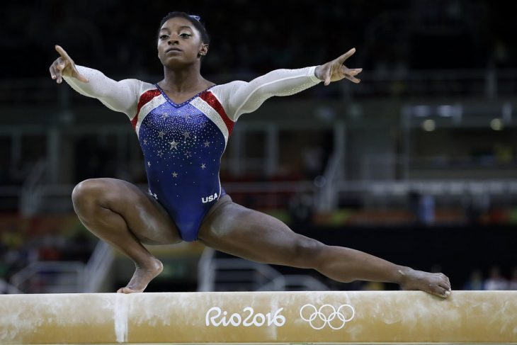mujer morena con traje sobre barra de gimnasia
