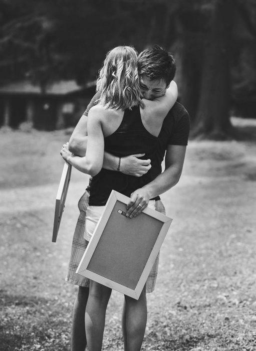 Chico abrazando a su esposa después de enterarse que sería papá en una sesión de fotos sorpresa
