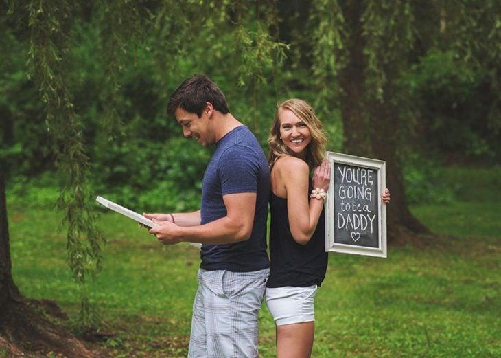 Chica que planeo una sorpresa para su marido sosteniendo una pizarra durante una sesión de fotos