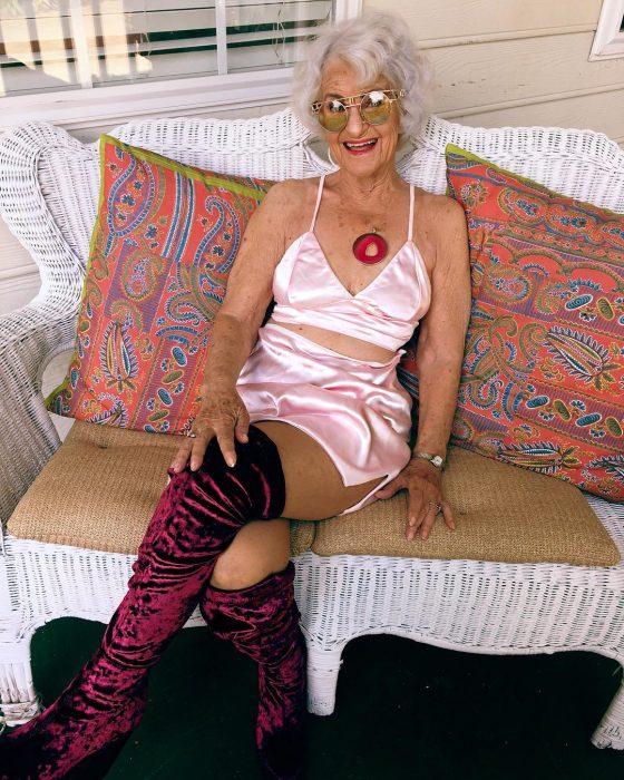Abuela dbaddiewinkle de 88 años usando unas botas hasta el muslo y un vestido color rosa mientras está sentada en un sofá