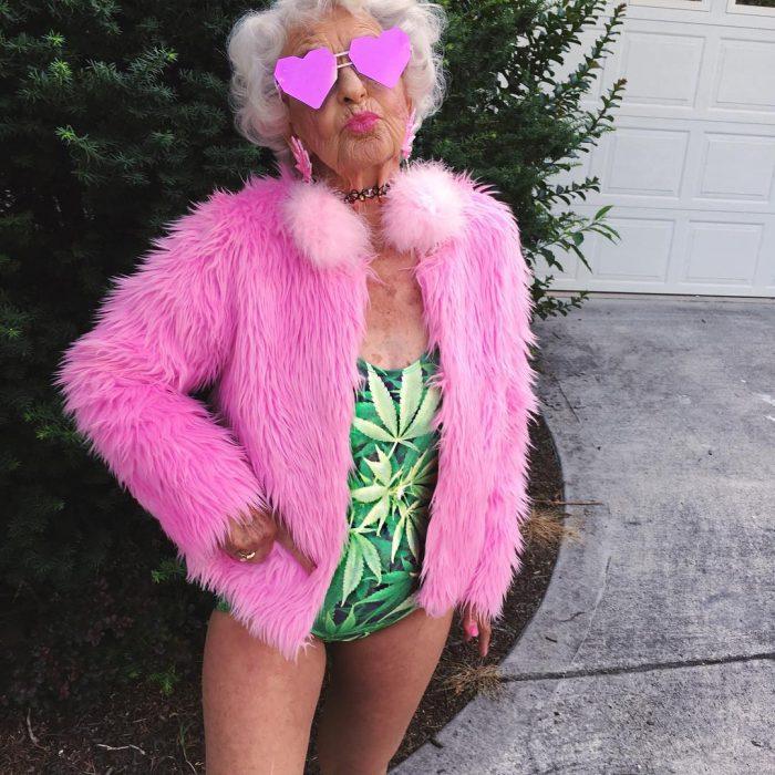 Abuela baddiewinkle de 88 años usando un traje de baño con una chaqueta color rosa y lentes de corazón