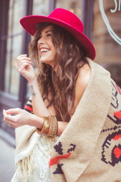 Chica usando un poncho y un sombrero rojo mientras está sentada en una banca riendo