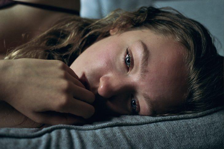 Chica recostada en la cama llorado