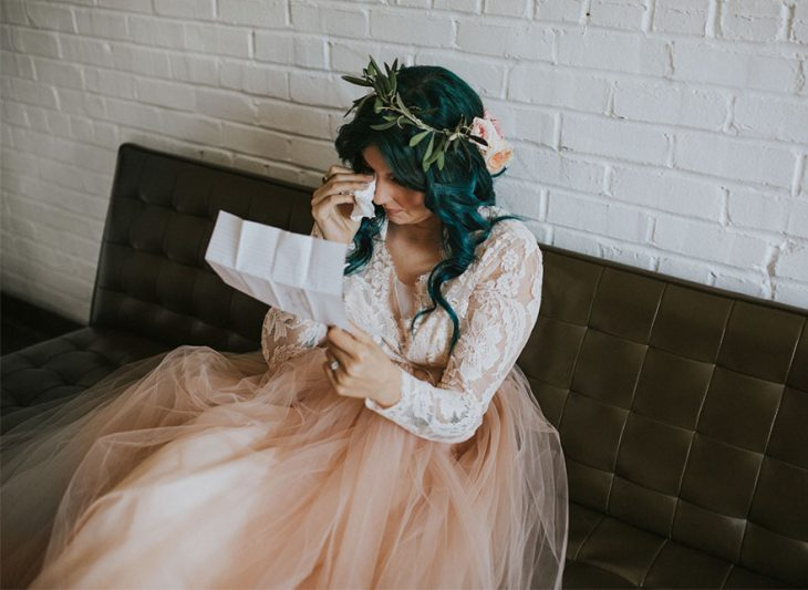 Chica sentada en un sofá leyendo una carta y llorando el día de su boda