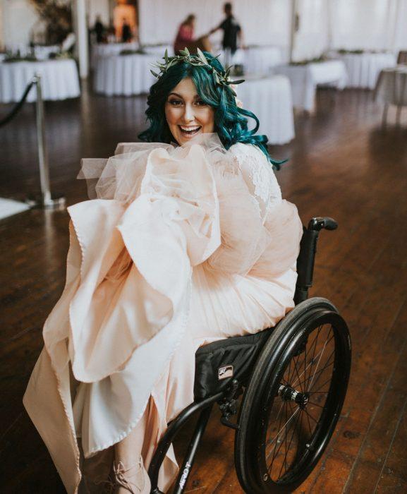 Chica en silla de ruedas mostrando su vestido el día de su boda