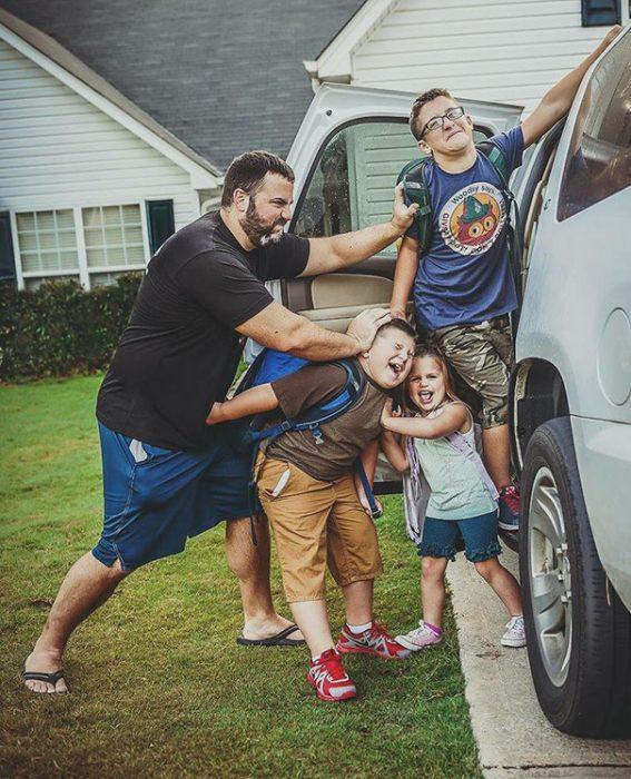 Papá mentiendo a sus hijos a la camioneta para el regreso a clases