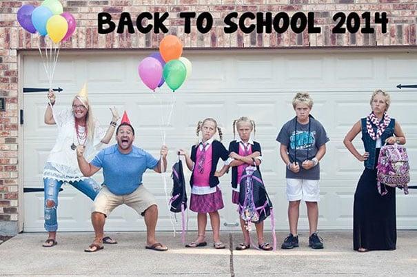 Padres celebrando con globos el regreso a clases de sus hijos