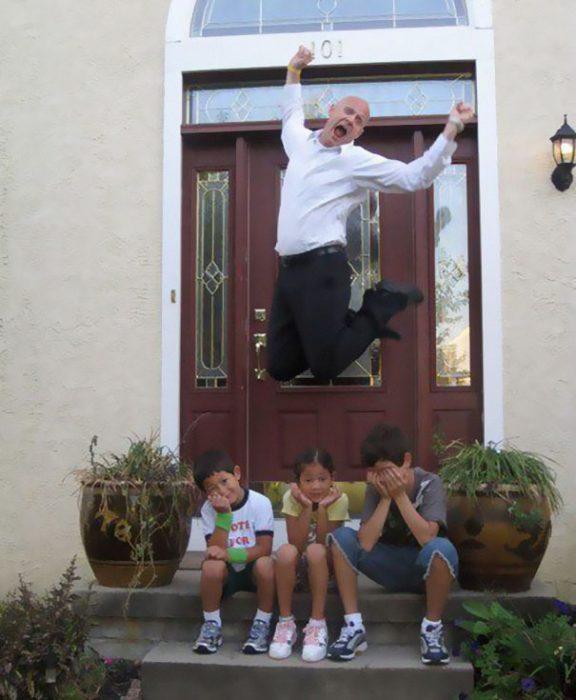 Padre saltando de alegría porque sus hijos vuelven a la escuala