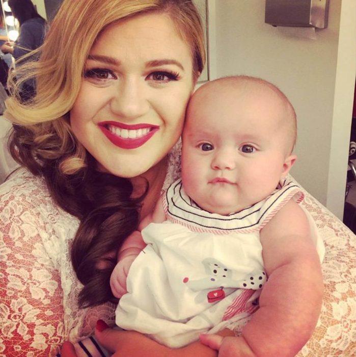 Kelly Clarkson sonriendo junto a su bebé