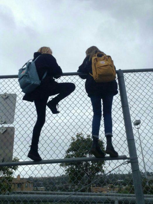 chicas escalando una reja