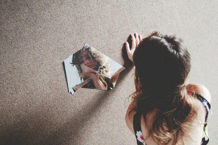 chica mirándose en espejo roto