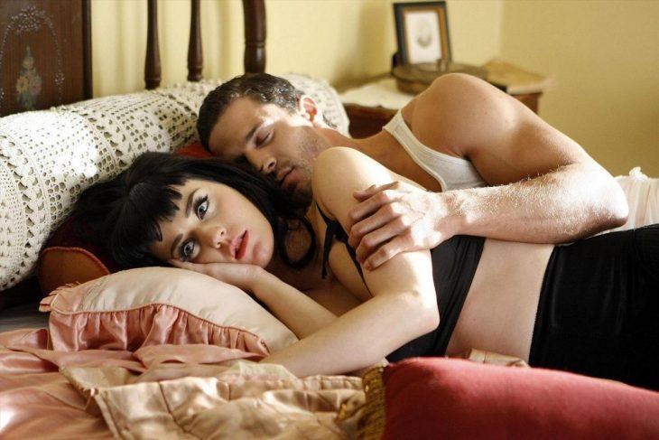 mujer blanca de cabello negro acostada y abrazada de hombre en la casa
