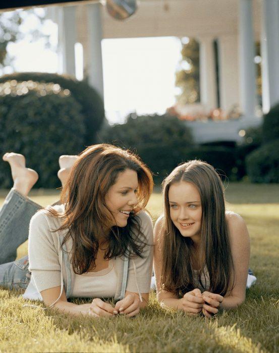 Escena de la serie gilmore girls chicas recostadas en el pasto