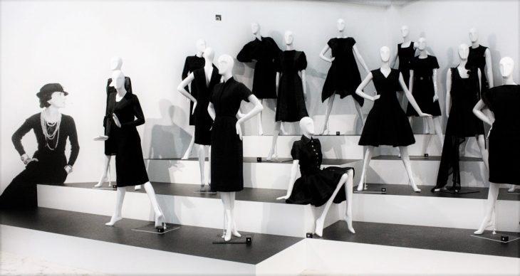 museo con maniquies y vestidos negros con mujer sentada