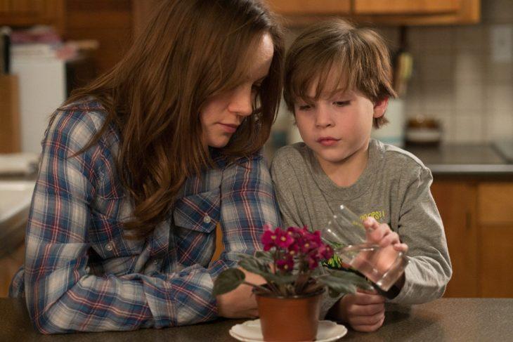 mujer blanca cabello castaño alimentando planta con niño