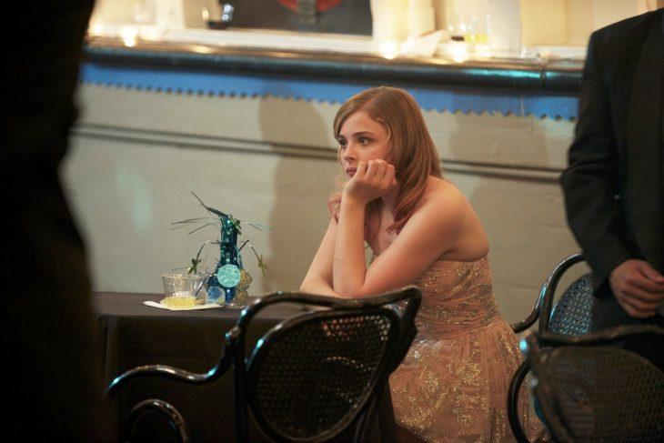 chica rubia sentada en una mesa