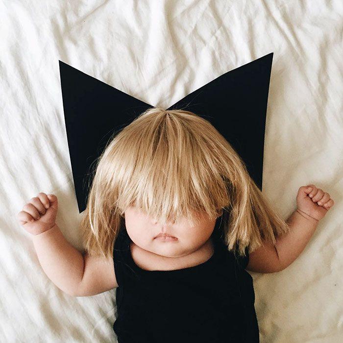 Bebé recostada en la cama disfrazada de la cantante Sia