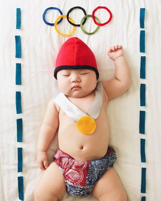 Bebé recostada en la cama disfrazada de ganador de medallas olímpicas
