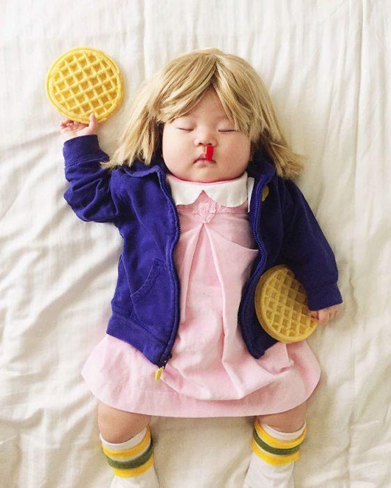 Bebé recostada en la cama disfrazada de once de stranger things