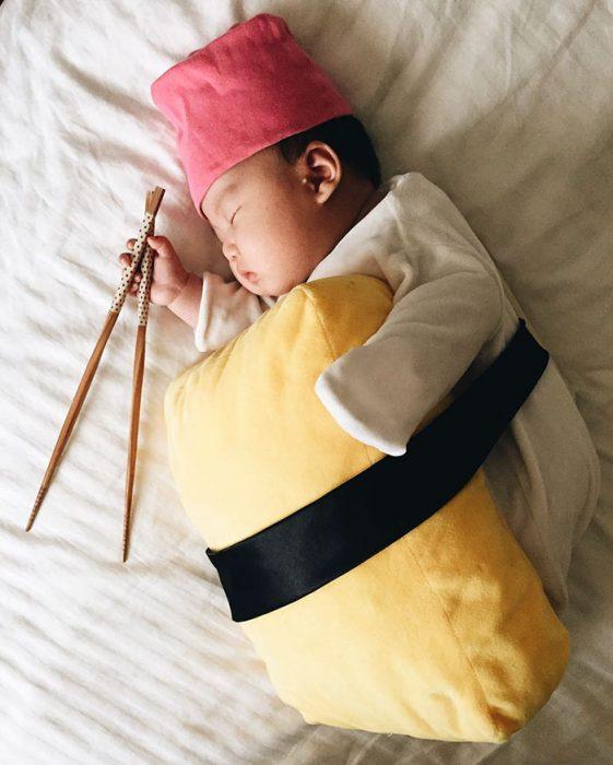 Bebé recostada en la cama disfrazada de sushi
