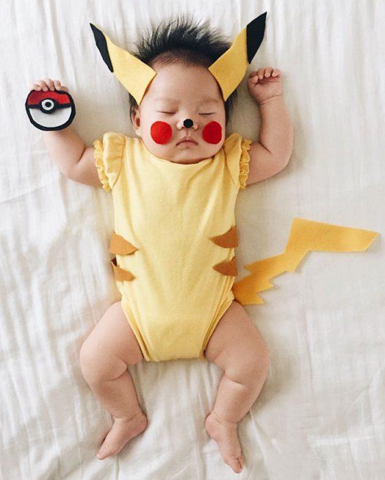 Bebé recostada en la cama disfrazada de pikachú