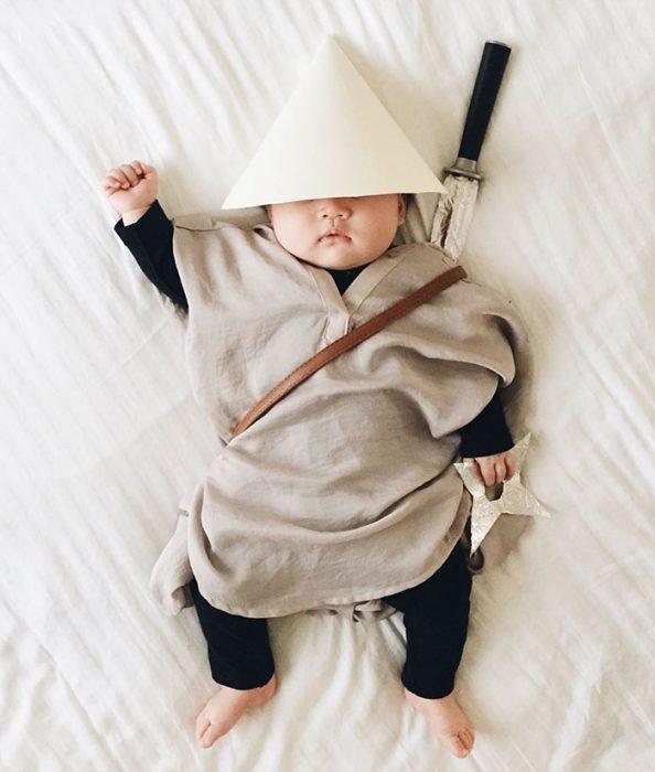 Bebé disfrazada de ninja recostada en la cama