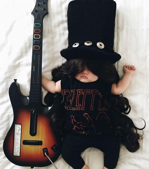Bebé disfrazada de slash con una guitarra recostada en la cama