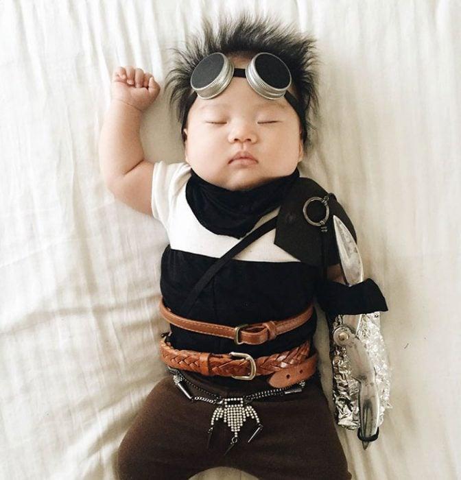 Bebé recostada en la cama disfrazada de Furiosa de Mad Max