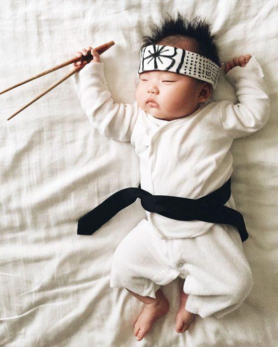 Bebé recostada en la cama disfrazada de Karate Kid