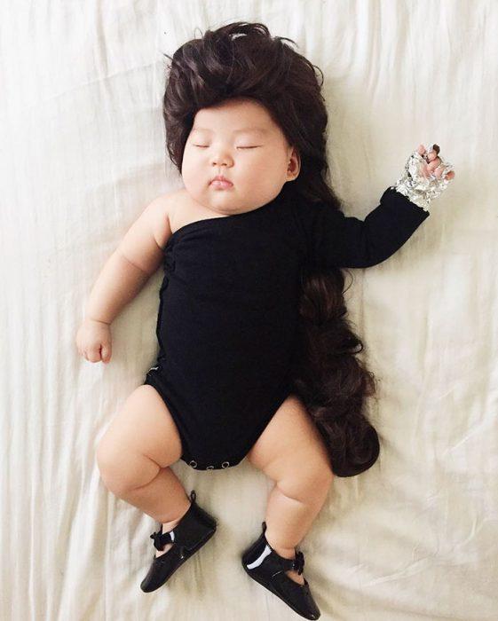 Bebé recostada en la cama disfrazada de Byonce