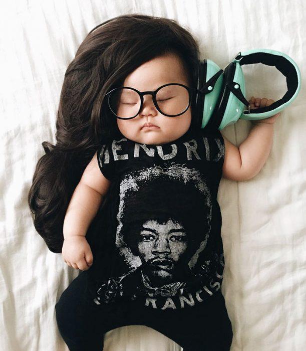 Bebé recostada en la cama disfrazada de Skrillex