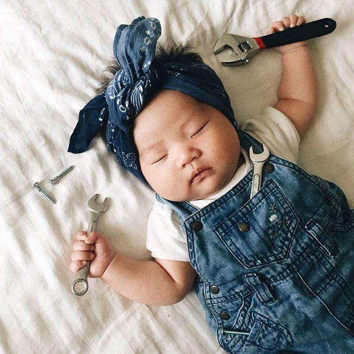 Bebé recostada en la cama disfrazada de mecánica