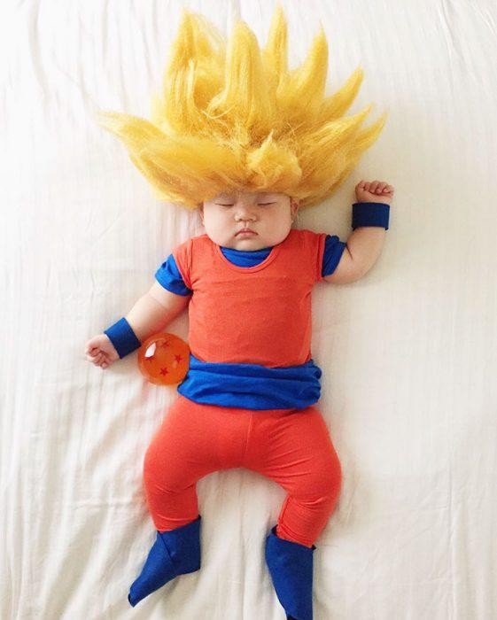 Bebé recostada en la cama disfrazada de goku
