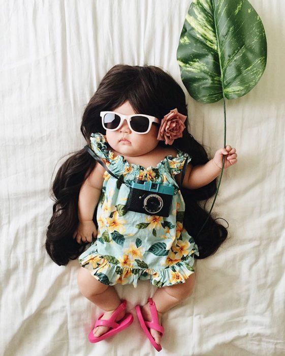 Bebé recostada en la cama disfrazada de turista en la playa