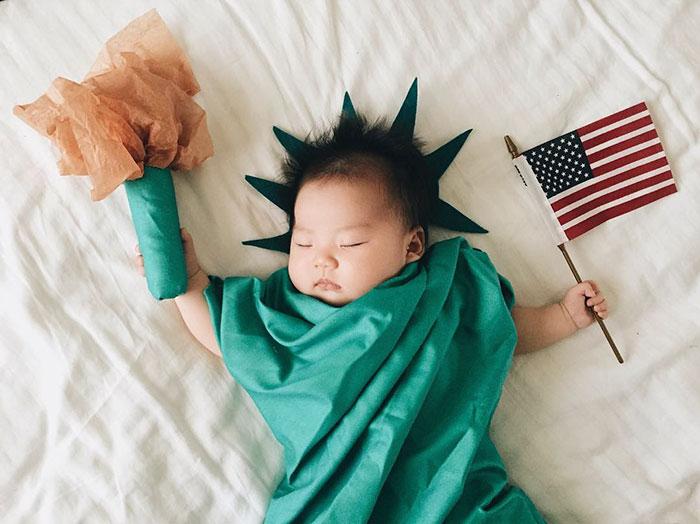 Bebé recostada en la cama disfrazada de estatua de la libertad