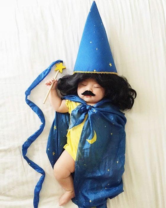 Bebé recostada en la cama disfrazada de mago
