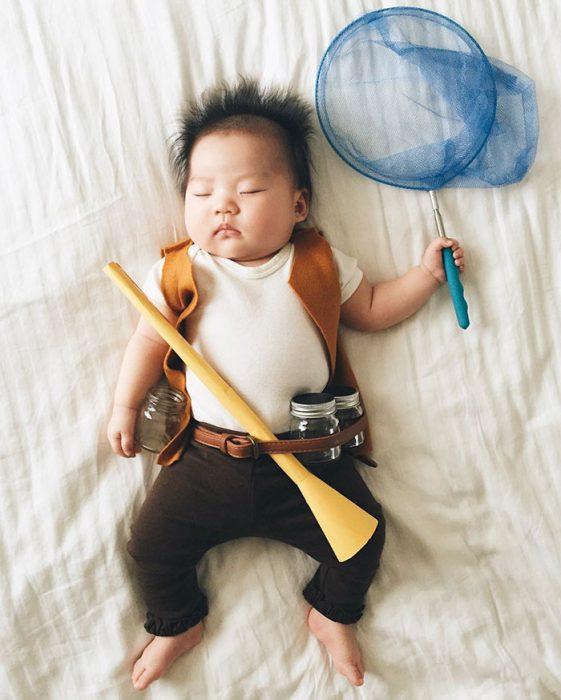 Bebé recostada en la cama disfrazada de cazador