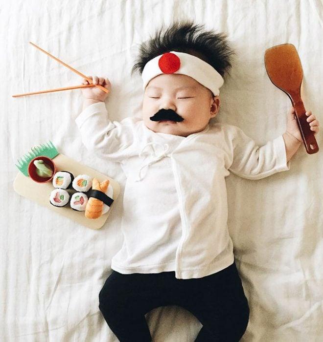 Bebé recostada en la cama disfrazada de cocinero de sushi