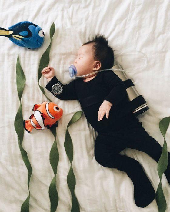 Bebé recostada en la cama disfrazada de buzo buscando a Dori