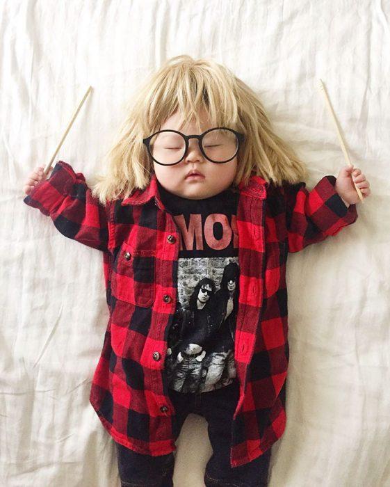 Bebé recostada en la cama disfrazada de Garth Algar del extraño mundo de Wayne