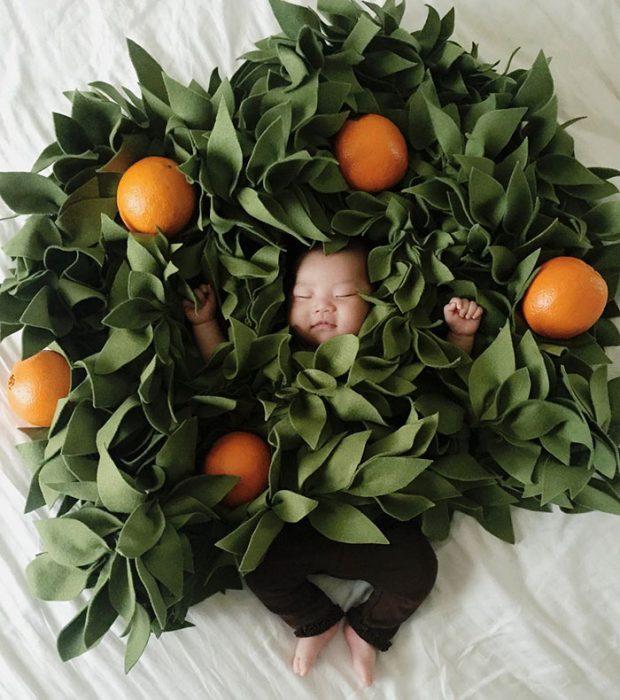 Bebé recostada en la cama disfrazada de árbol de naranjas